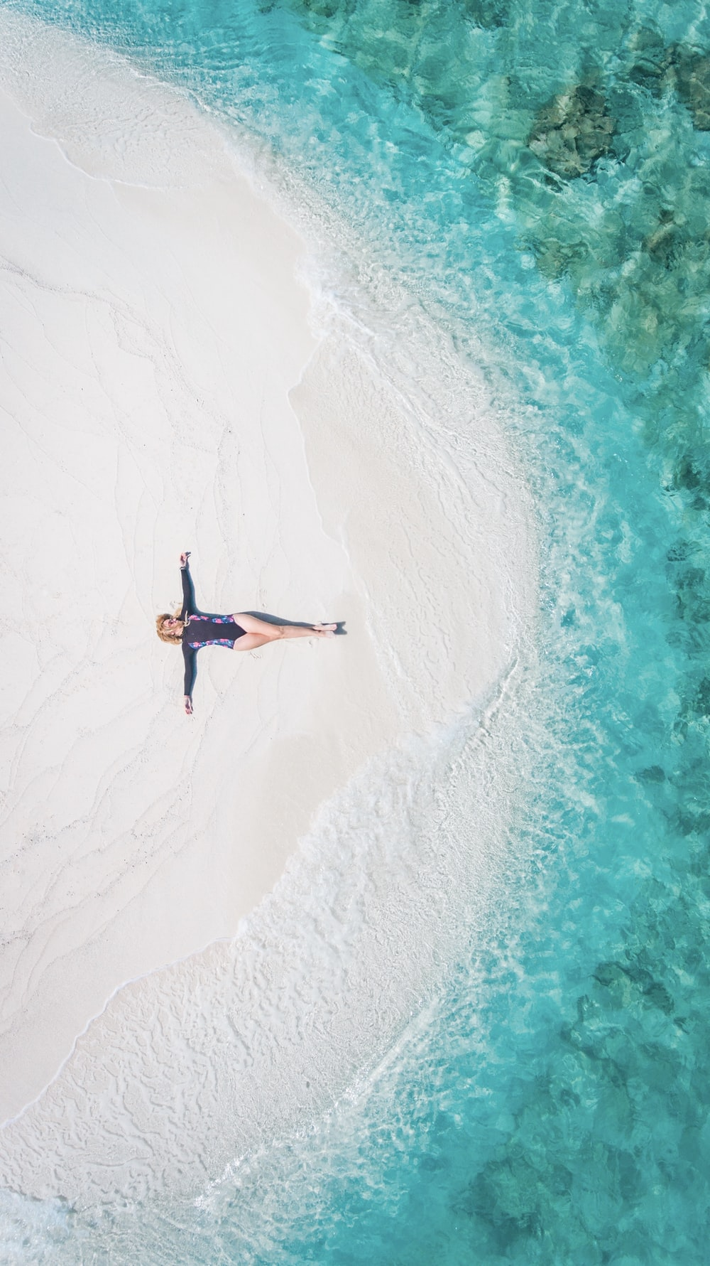woman lying down on white sand