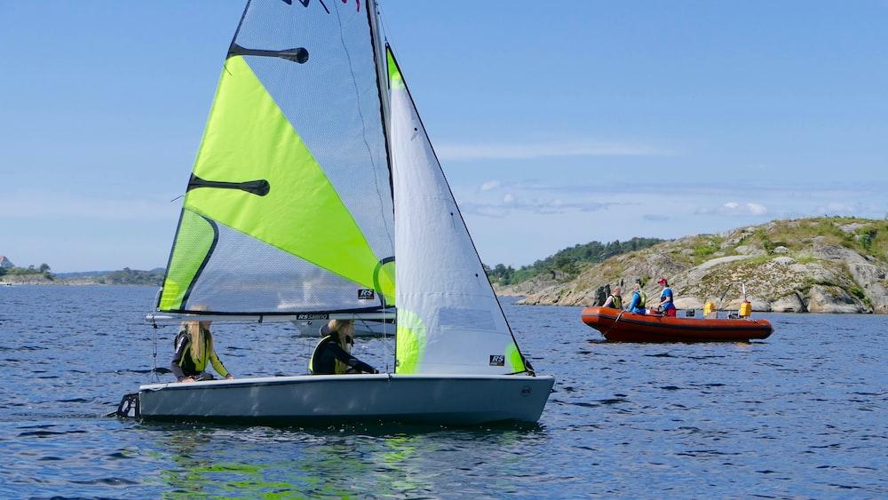 two person riding on white sailboat