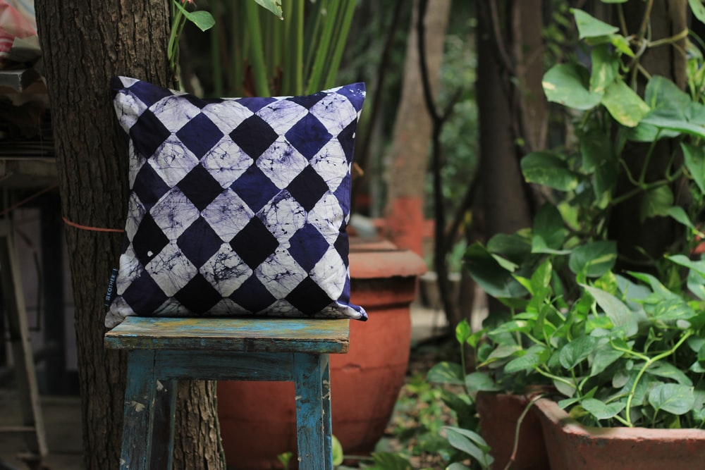 white, black, and purple harlequin throw pillow on square stool