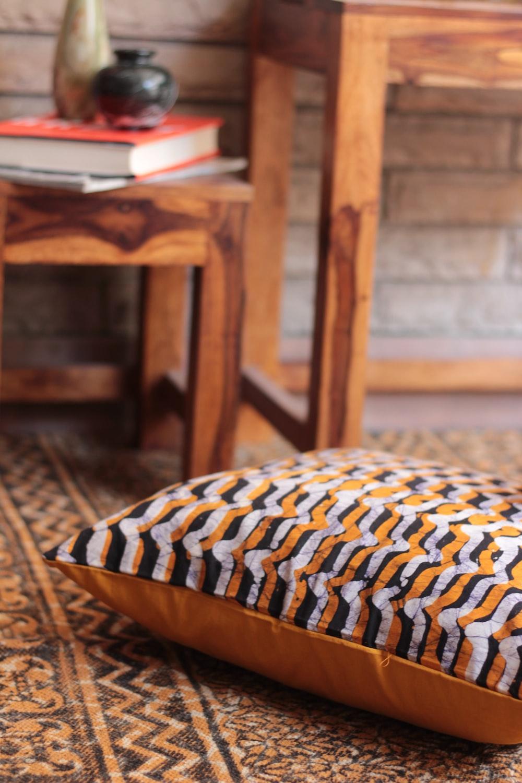 selective focus photo of white, black, and orange throw pillow