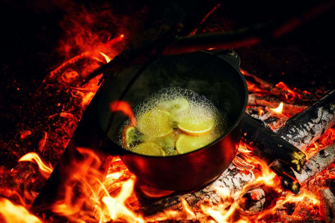 The cauldron is boiling on the coals of the fire. In a camping boiler on a halt, mulled wine with lemon and spices is cooked.