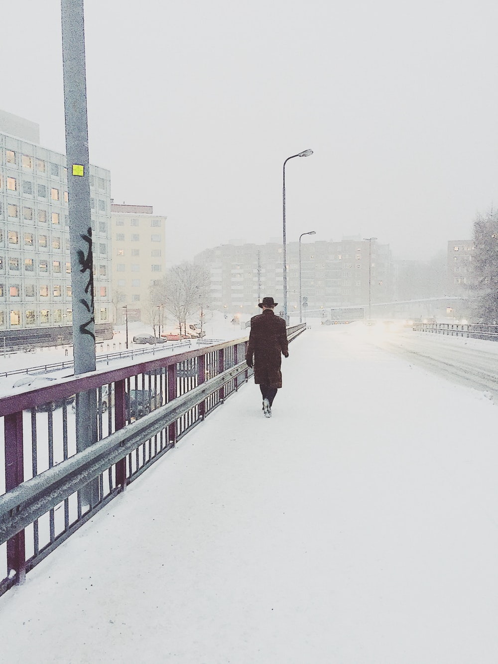 woman walking on bridge covered with snow