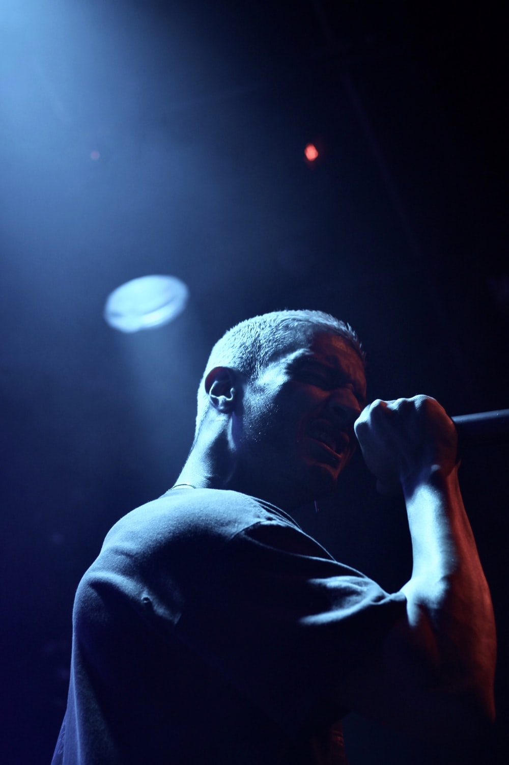 man holding microphone performing on stage
