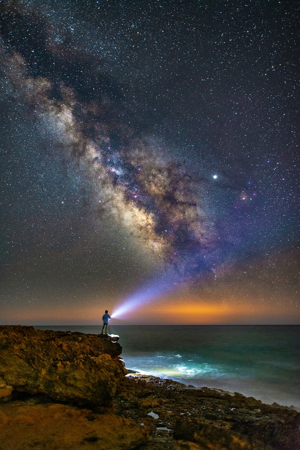 person standing near cliff holding flashlight overlooking milky way