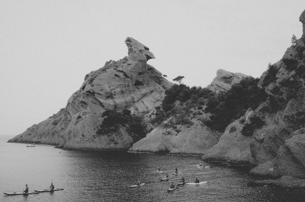 grayscale photo of group of people on clam body of water in front of rock formation