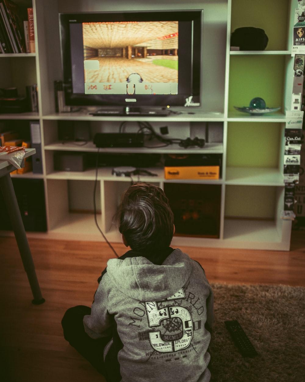 boy sitting on floor infront of TV