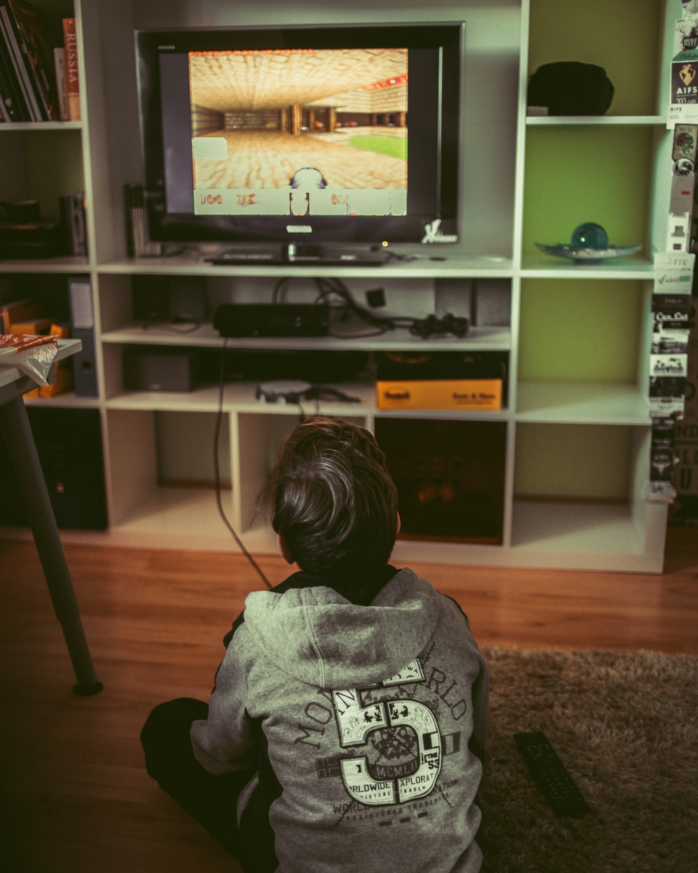 boy sitting on floor infront of TV