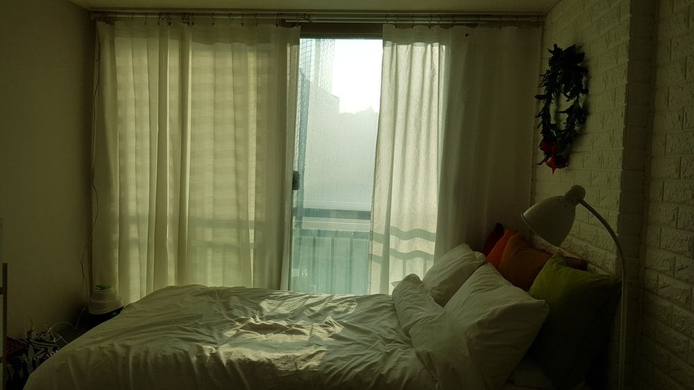 white bedspread on bed beside window