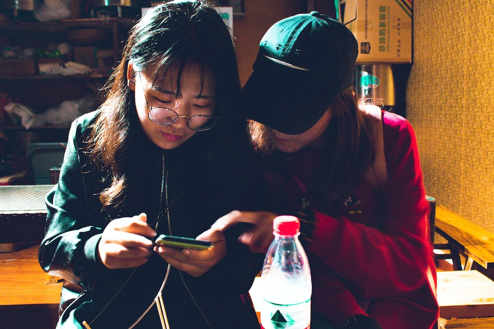 two women looking at a smartphone