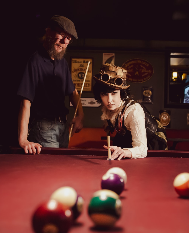 woman playing billiard near man