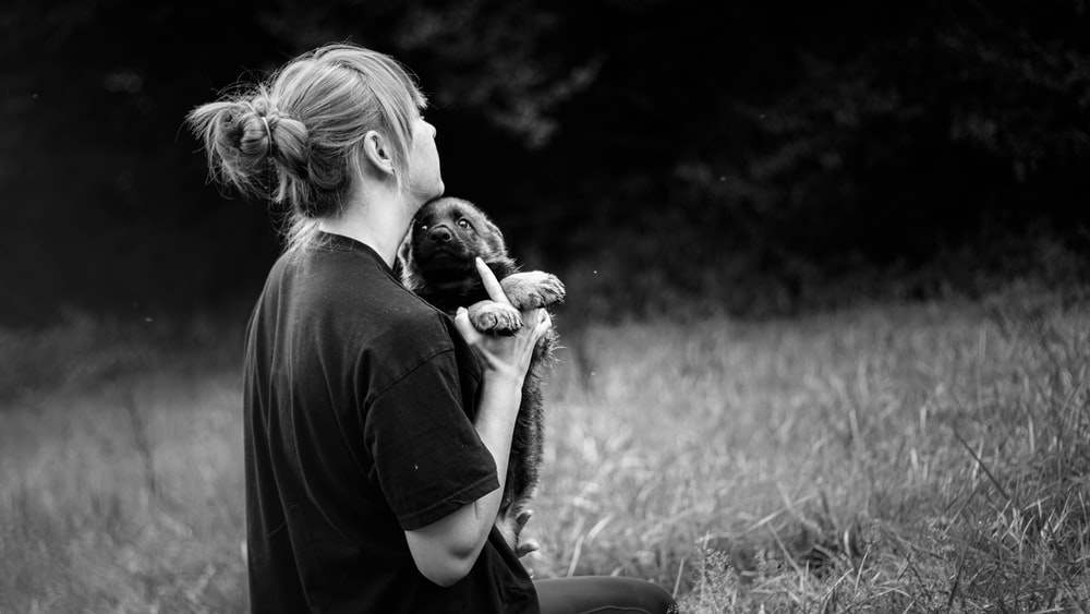 grayscale photo of person holding puppy