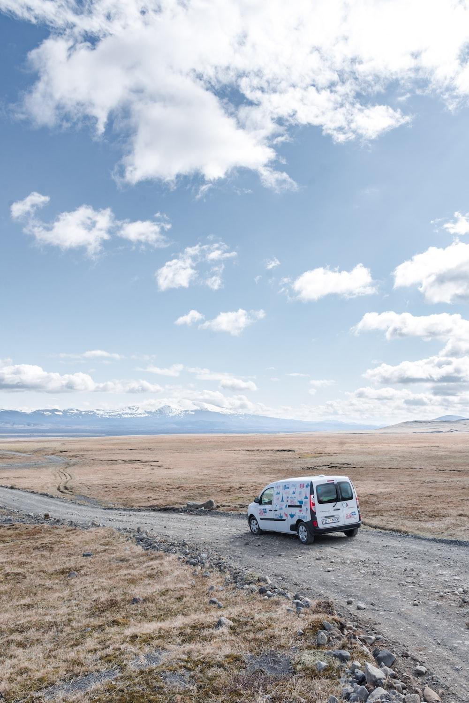 white van passing by desert during daytime