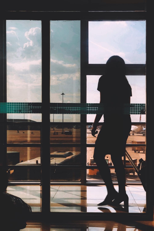 silhouette photography of person standing beside door