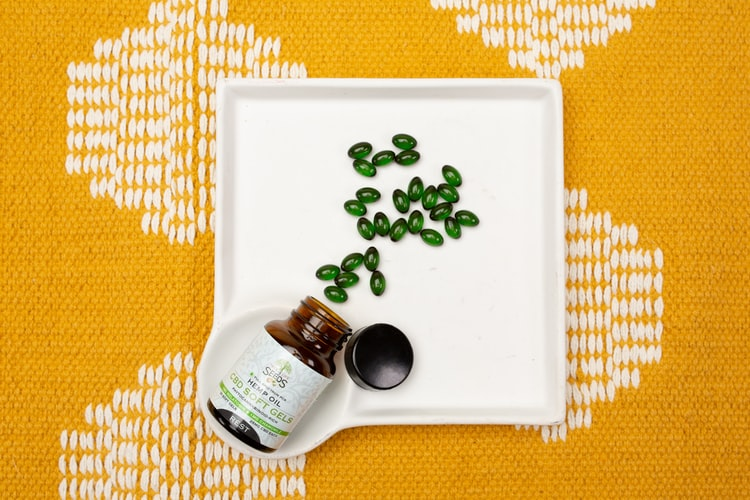 "A white tray with green gel capsules spilled out of it and a bottle labelled ""hemp oil"", all on top of a yellow tablecloth"