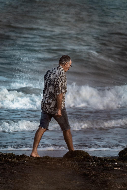 man walking near the body of water photograph