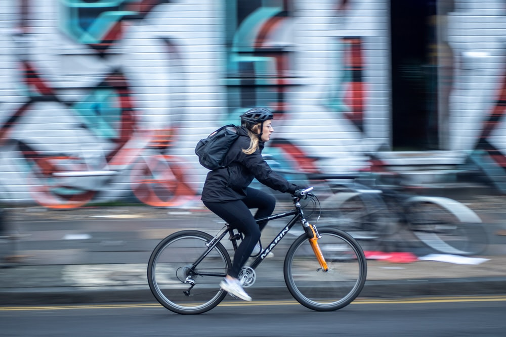 time-lapse photography of woman riding a bicycle