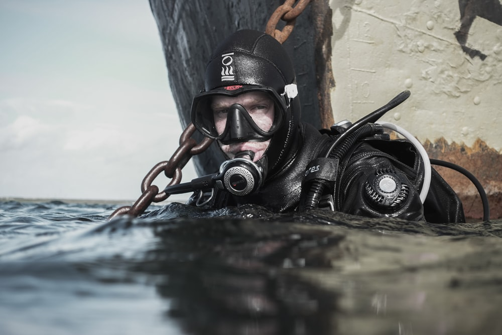 man wearing scuba diving on body of water