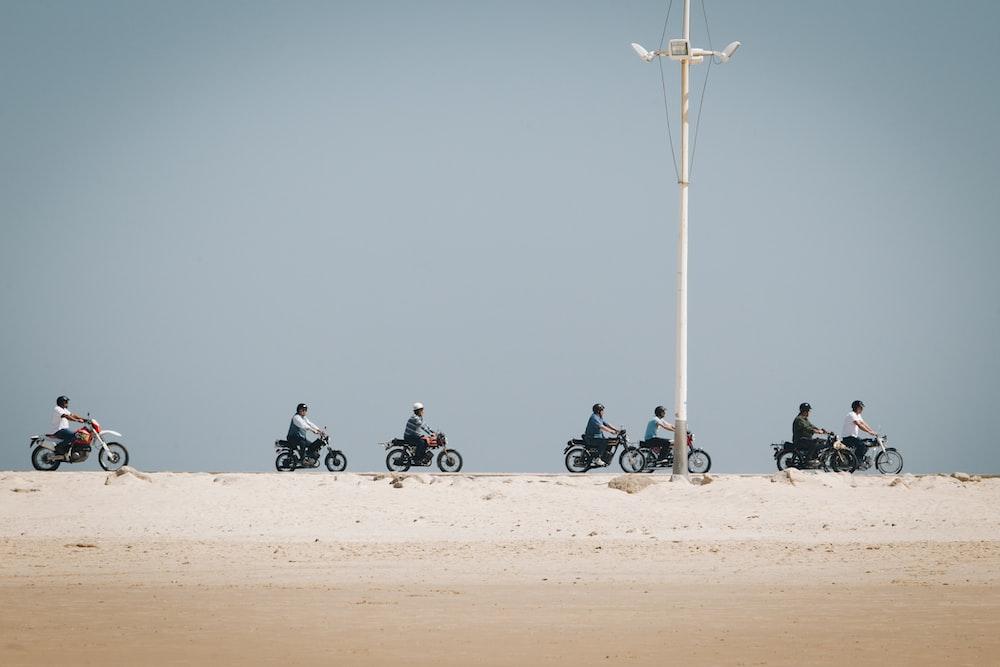 seven men riding motorcycle on desert