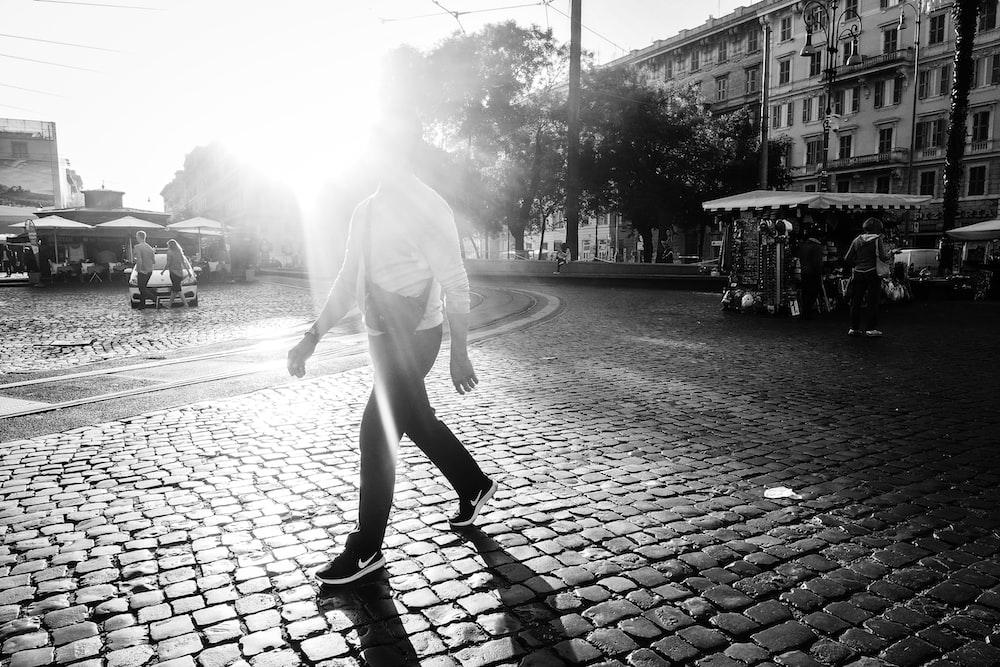 grayscale photo of man walking on brick pavement
