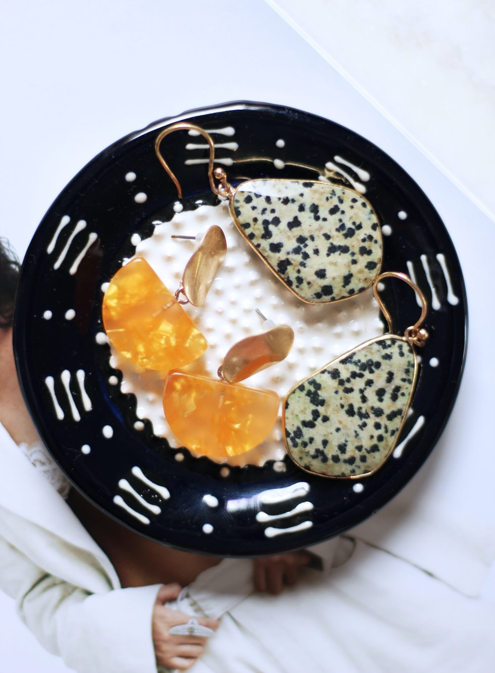 pair of gold-colored and white earrings