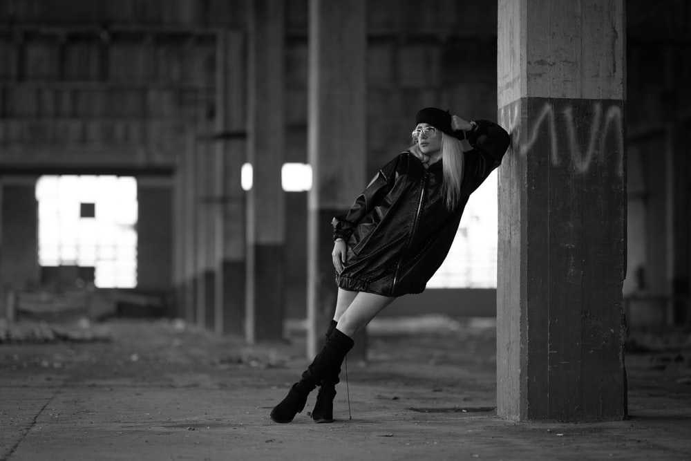 grayscale photo of woman standing and leaning on concrete post