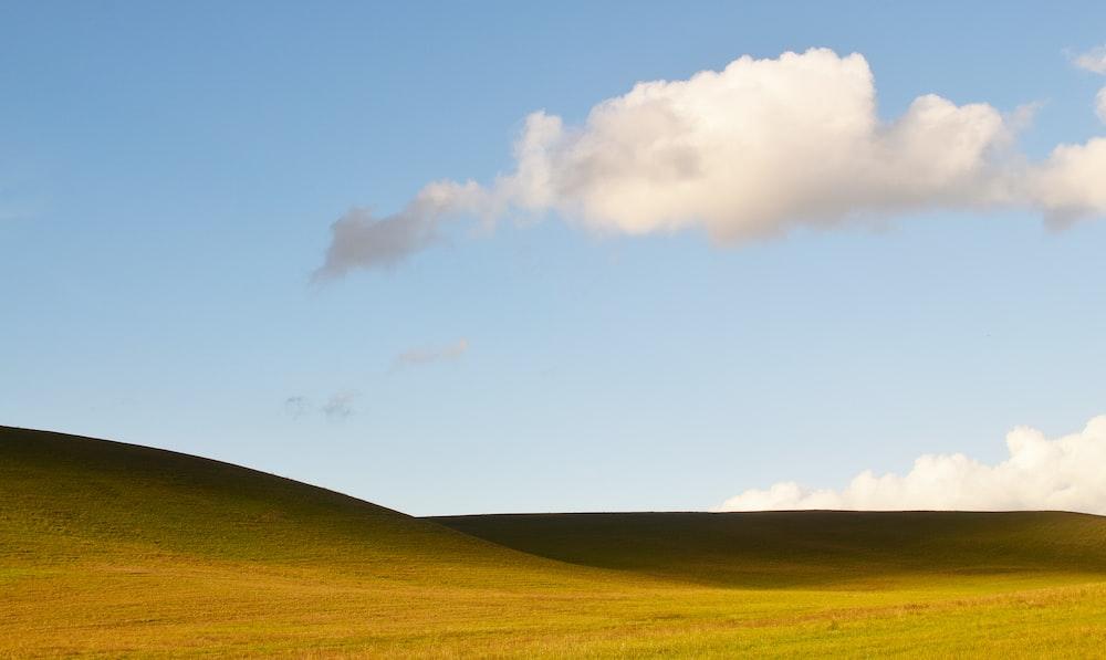 green hills under clouds during daytime