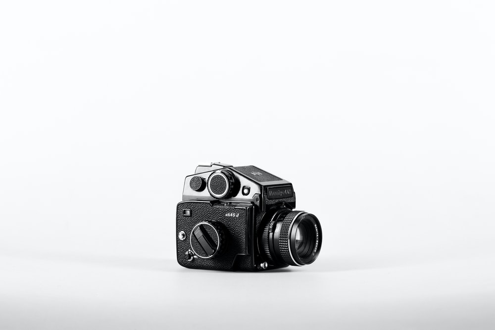 gray and black camera on white surface