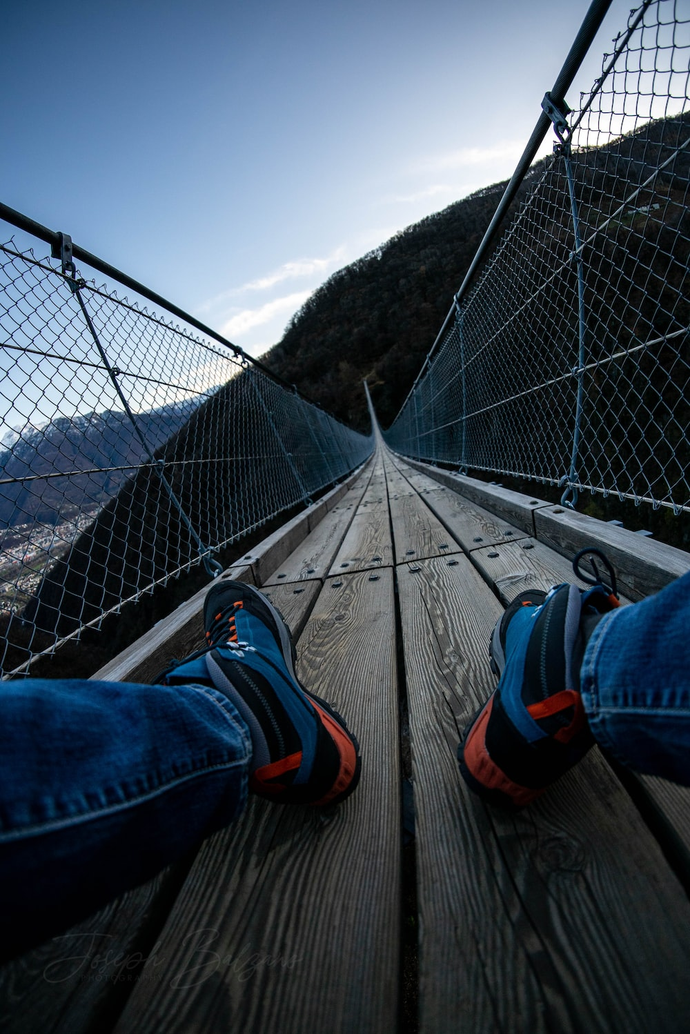 person sitting on bridge during day