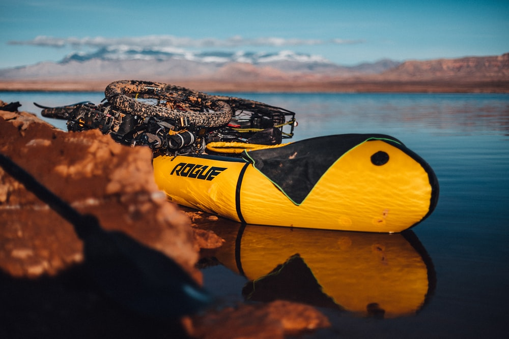 yellow and black Rogue inflatable boat carrying bicycle