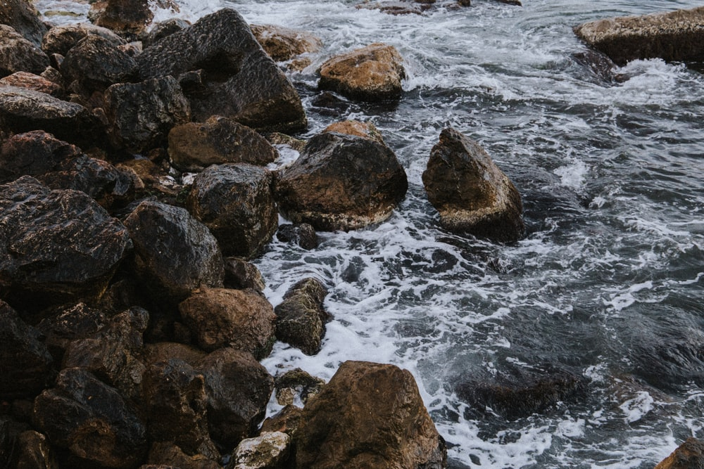 brown stones on body of water