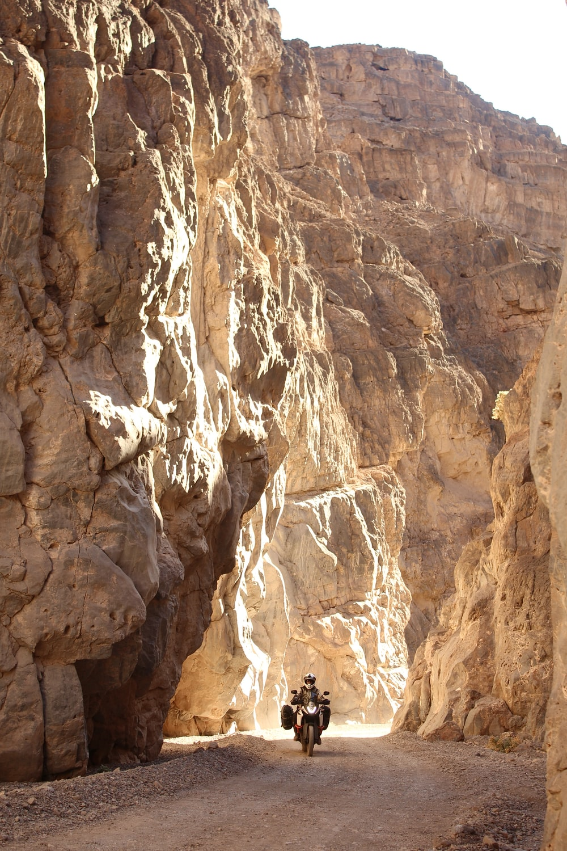 man riding motorcycle near rock mountain
