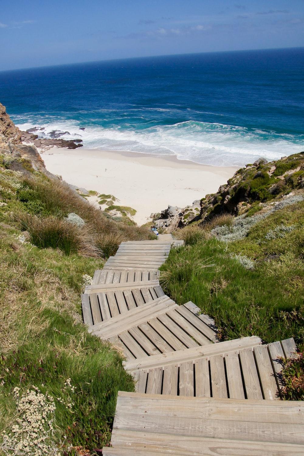 brown wooden stairs to blue ocean