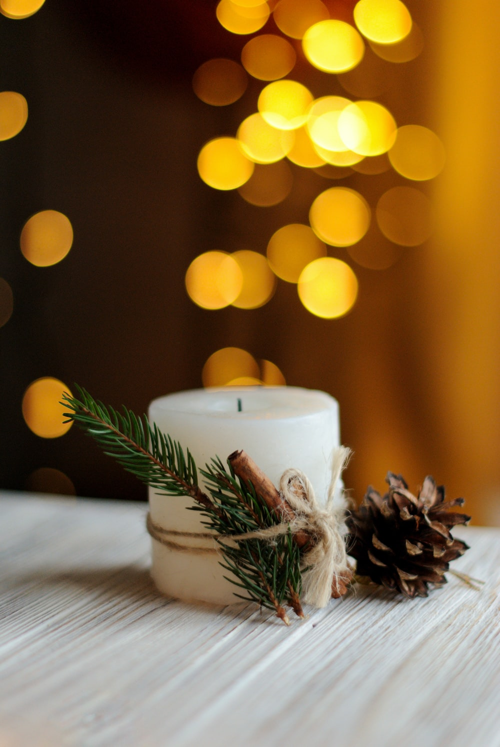 white pillar candle with pinecone