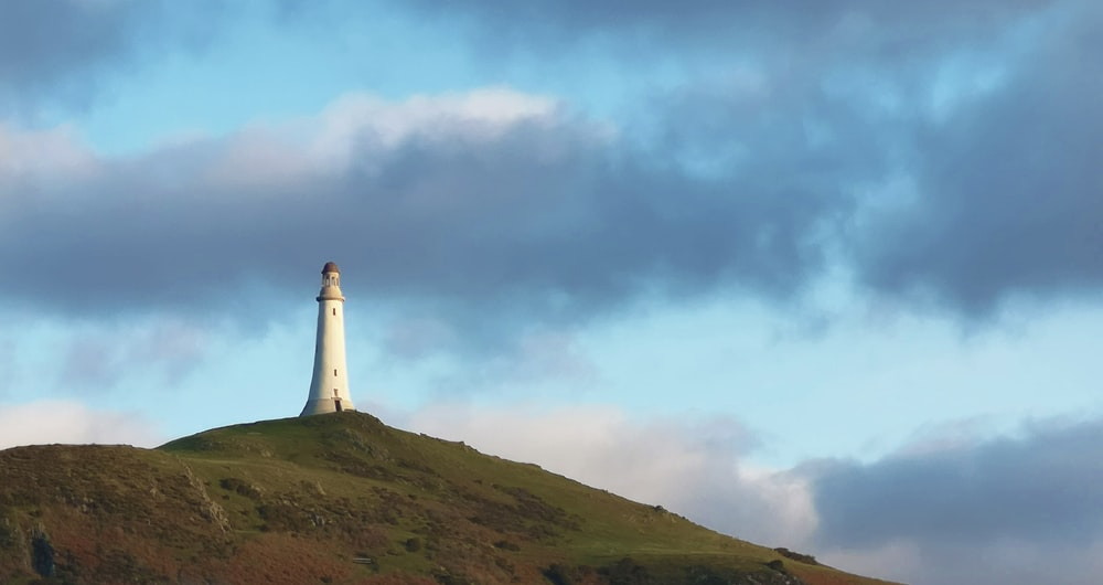 white lighthouse on top of hill