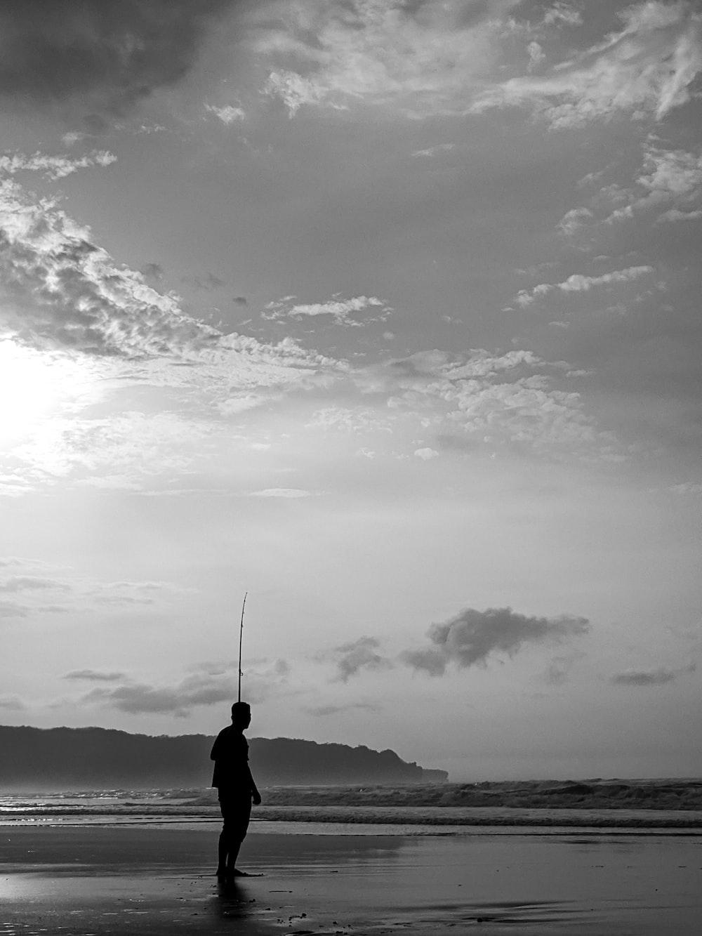 grayscale photography of man on seashore