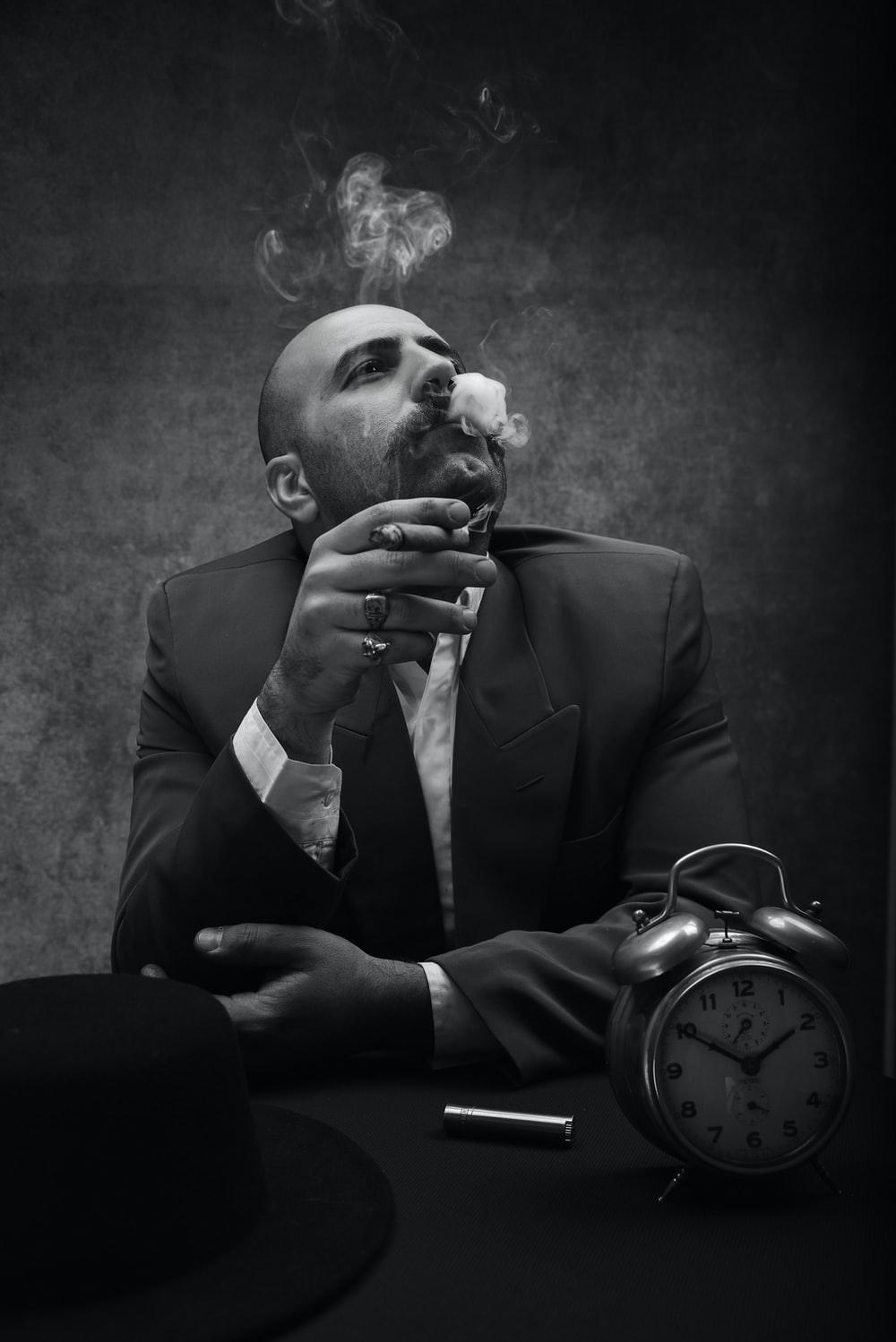 man wearing black suit sitting by the table while smoking