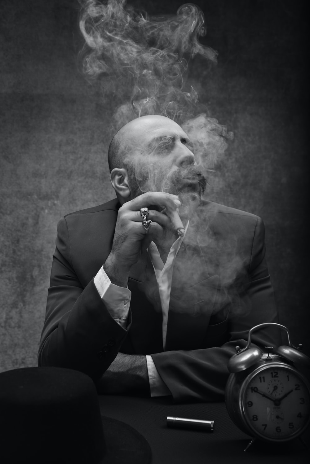 man wearing black suit sitting by the table smoking