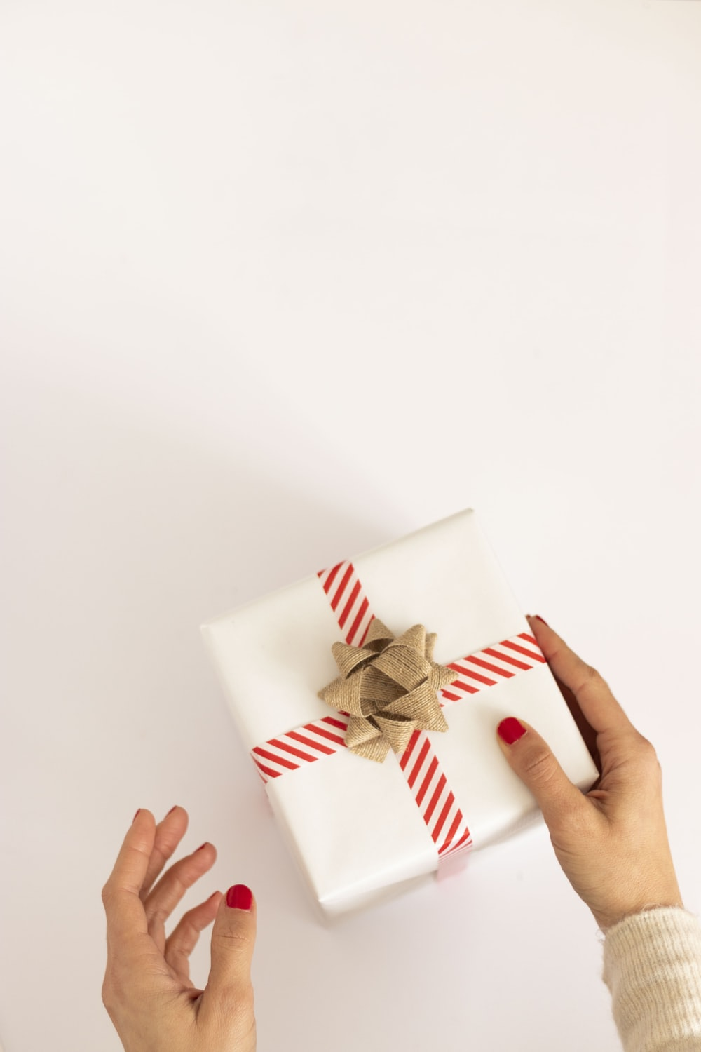 person holding white and red gift box