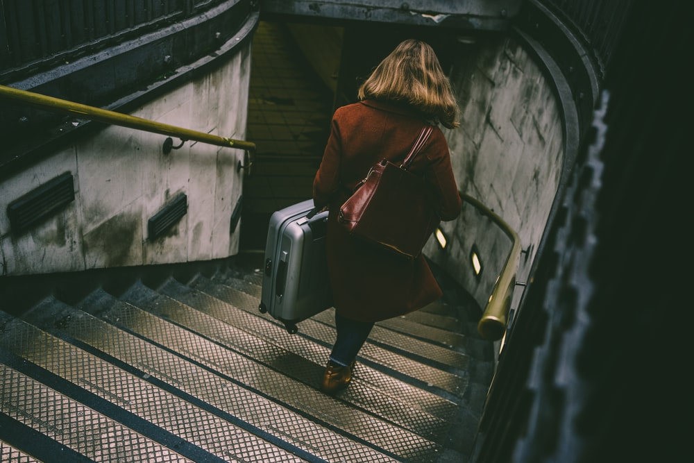 woman walking on stairway while holding luggage