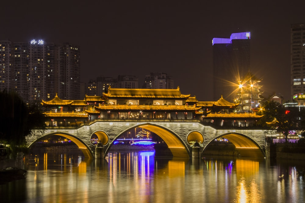photography of building and bridge during nighttime