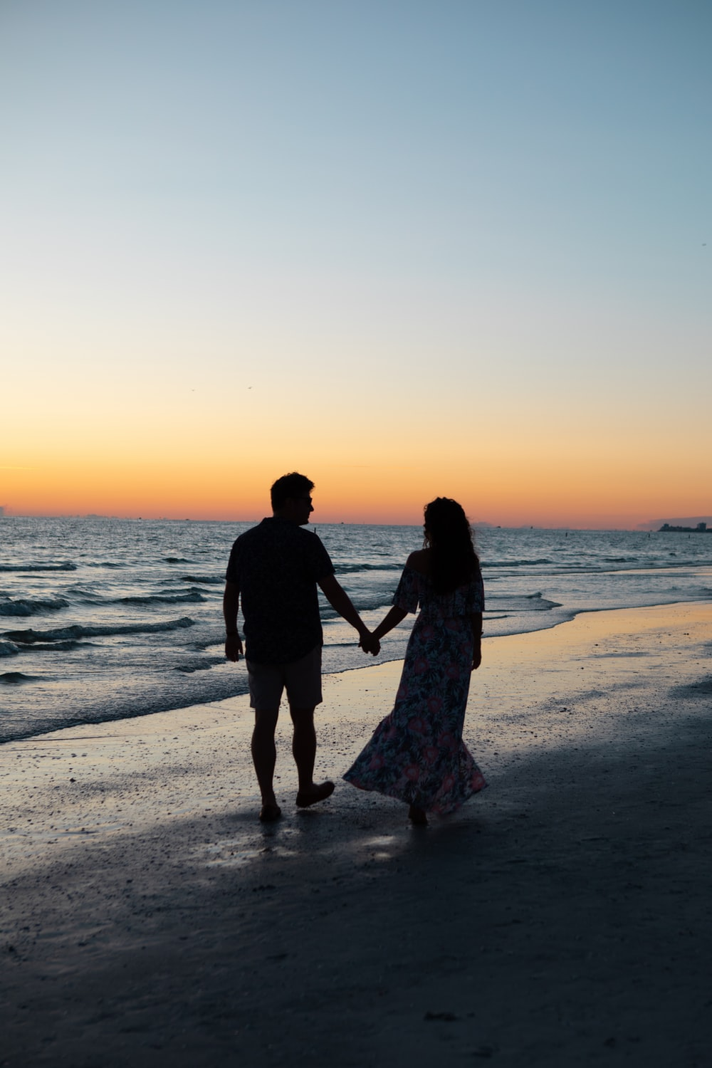 photography of man and woman holding hands each other while walking beside seashore