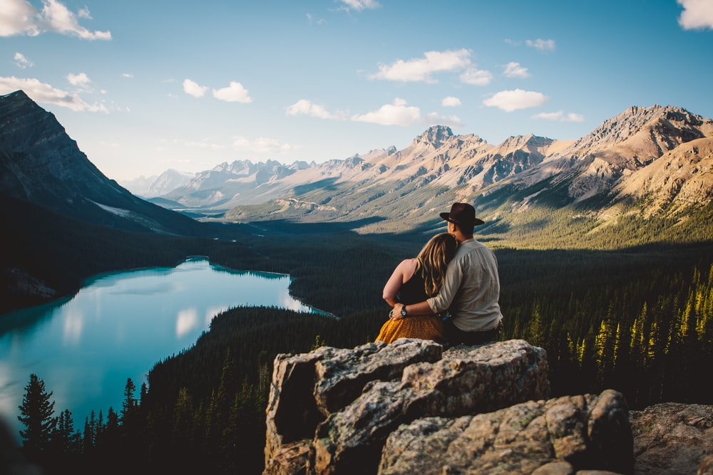 woman and man sitting on the cliff facing the river