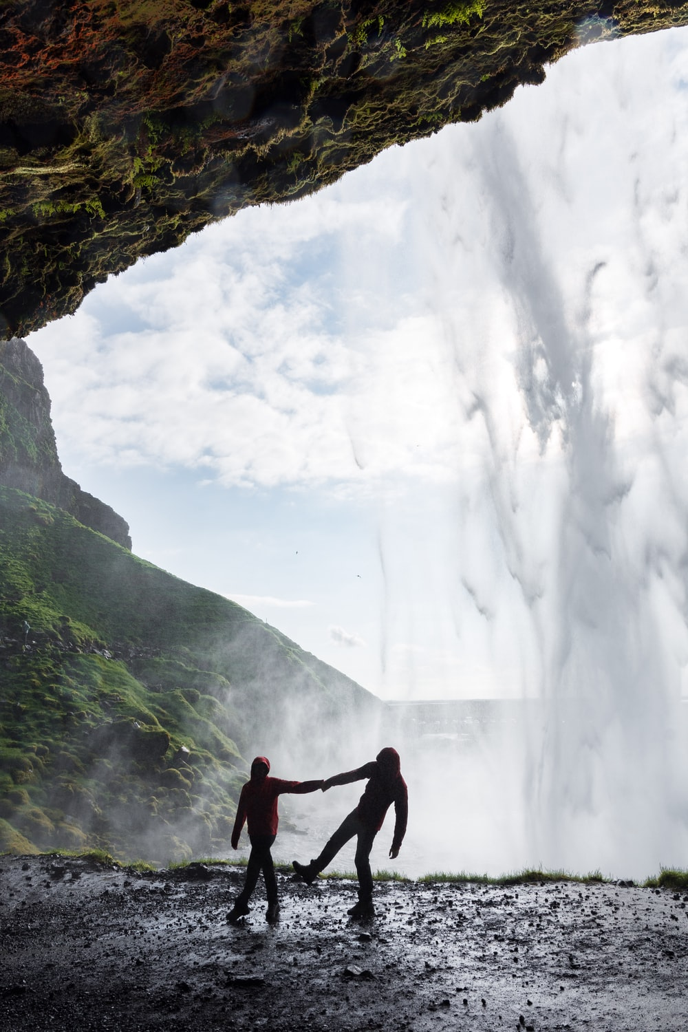 silhouette of man and woman holding each other hands under the cave with waterfalls