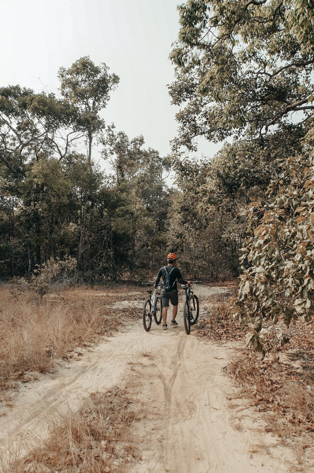 man walking while holding on to two bicycles