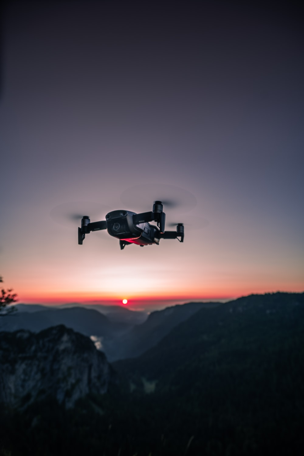 view photography of black quadcopter drone on air during dawn