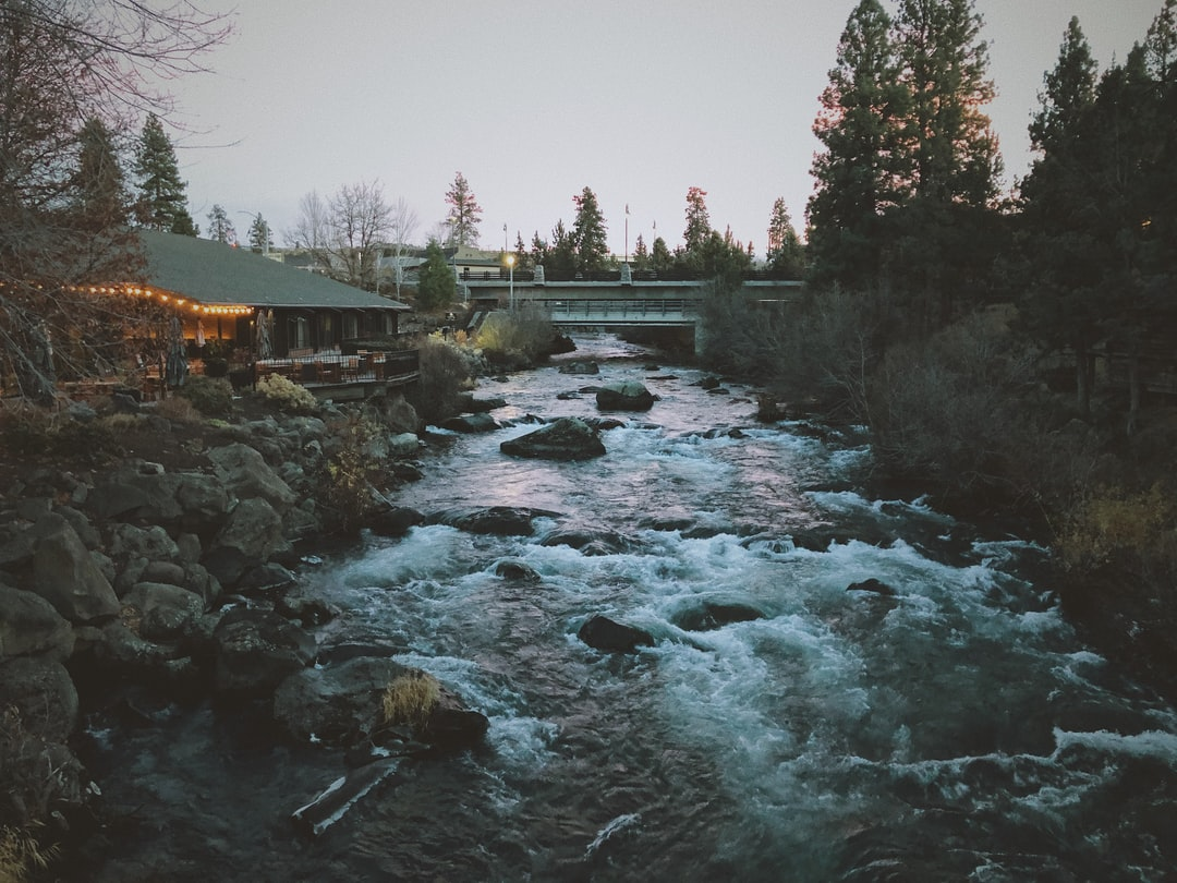 A moody evening shot of a flowing white water river over rocks with evergreen trees and a bridge and lodge in the background.