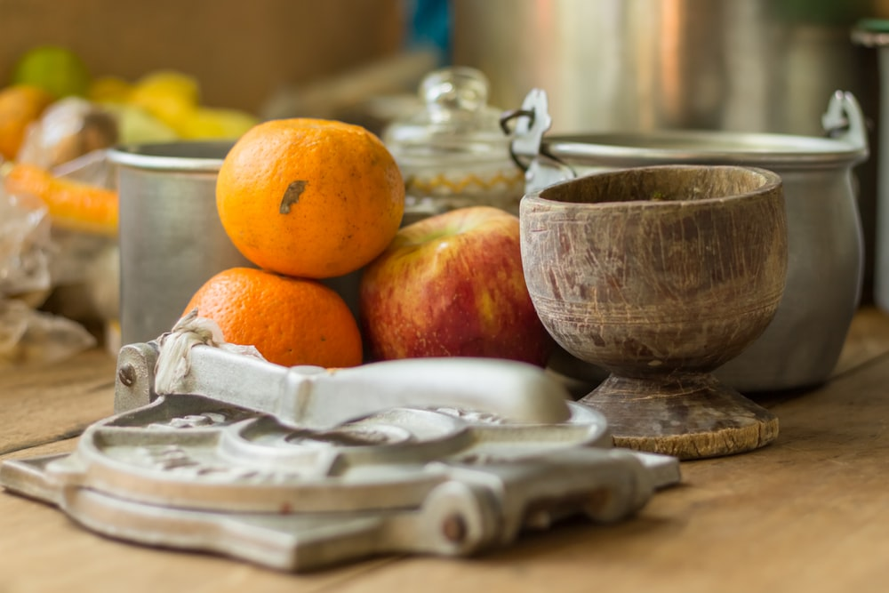 selective focus photography of oranges and apple by pots