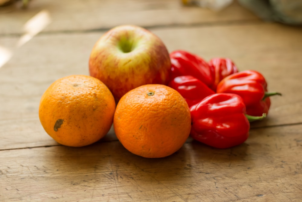 2 oranges, apple, and 5 peppers on wooden surface