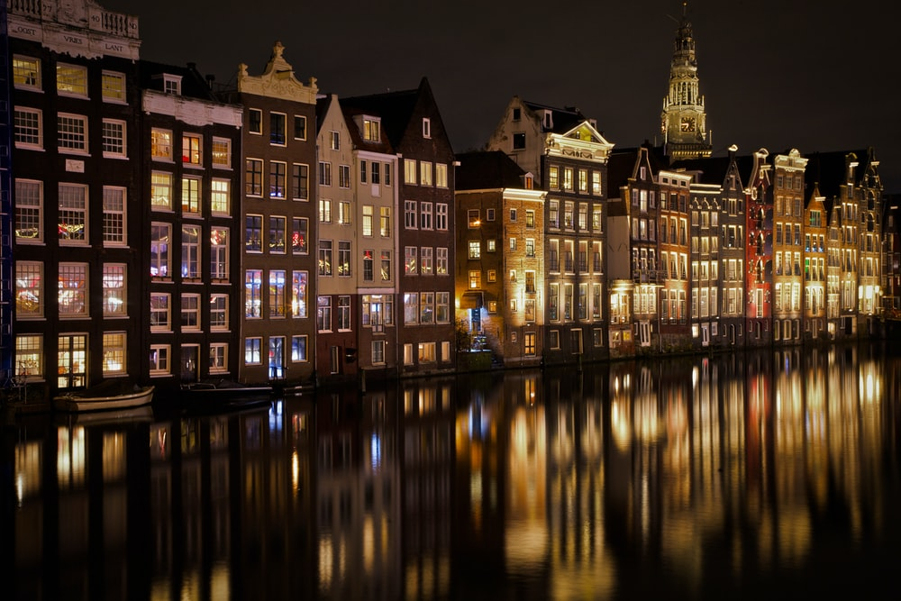 view photography of lighted buildings near sea during nighttime
