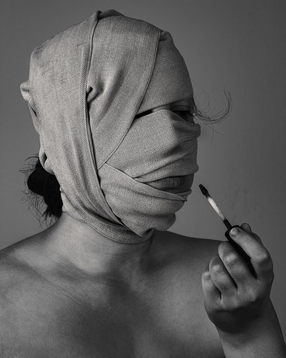 grayscal photo of woman with bandage on face